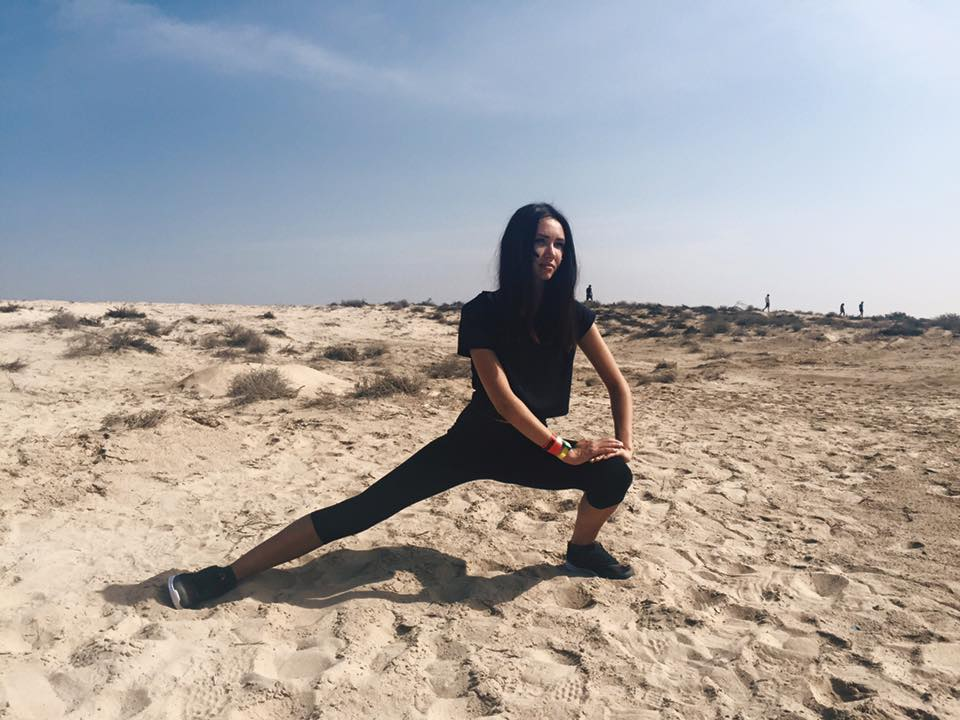 Mariia Yevdokmova stretches on the dunes of the beach.