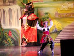 A Dance with Us student and the life-size bull puppet in the Spanish Variation